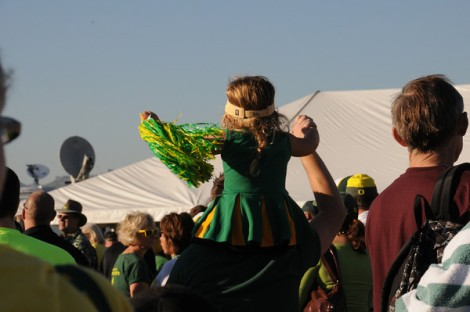 Little girl cheerleader in an Oregon Ducks outfit on her dad's shoulders